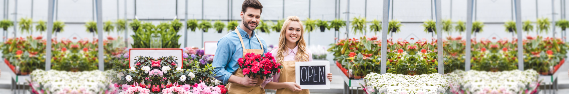 portrait of man holding flowers and woman holding open signage